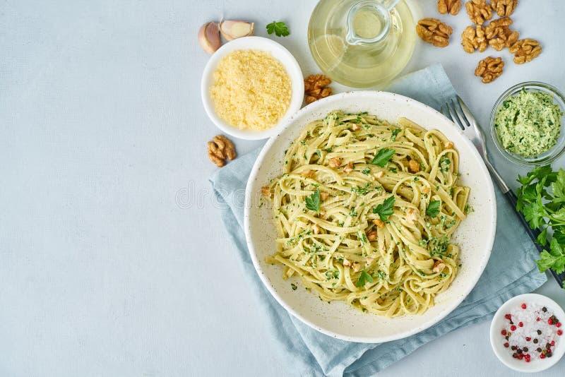 Ζυμαρικά Pesto, bavette με τα ξύλα καρυδιάς, μαϊντανός, σκόρδο, καρύδια, ελαιόλαδο Η τοπ άποψη, αντιγράφει το διαστημικό, μπλε υπ στοκ εικόνες