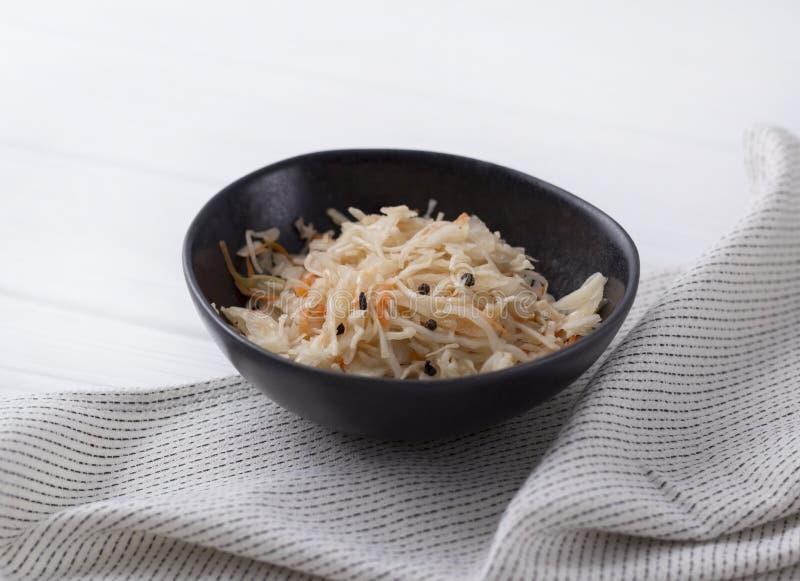 Ζυμωνομμένο λάχανο Παραδοσιακό ρωσικό sauerkraut ορεκτικών με το καρότο στο πιάτο τεχνών στον άσπρο ξύλινο πίνακα στοκ εικόνες
