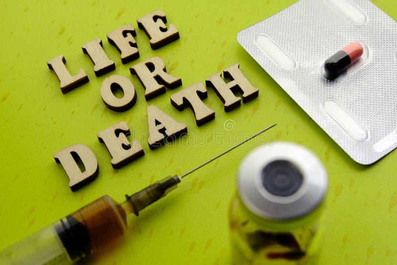 Ζωή ή θάνατος επιγραφής από τις ξύλινες επιστολές δίπλα σε ένα χάπι, σύριγγα, μπουκάλι ιατρικής σε ένα πράσινο υπόβαθρο Ιατρική έ στοκ εικόνα