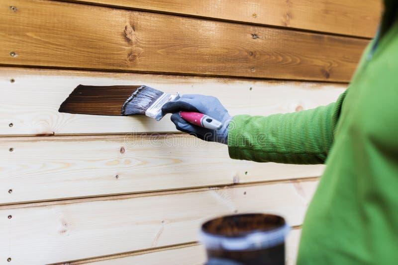 Ζωγράφος με το πινέλο που χρωματίζει την ξύλινη πρόσοψη σπιτιών στοκ φωτογραφίες