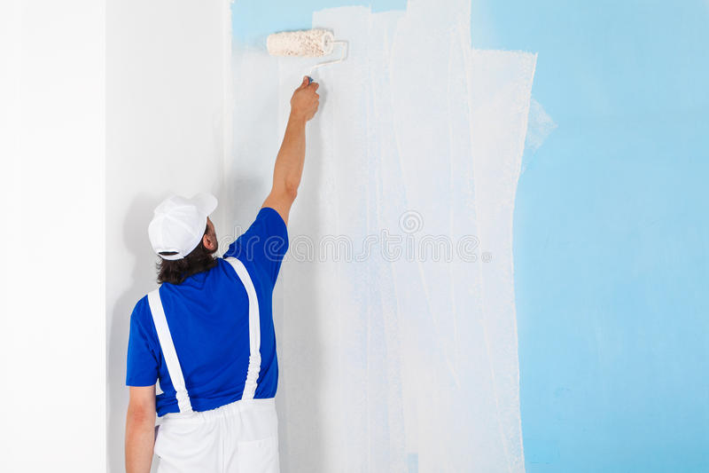 Ζωγράφος που χρωματίζει έναν τοίχο με τον κύλινδρο χρωμάτων στοκ φωτογραφίες