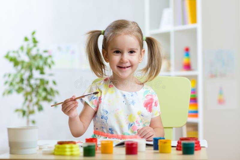 Ζωγραφική κοριτσιών παιδιών χαμόγελου στον παιδικό σταθμό στοκ εικόνες