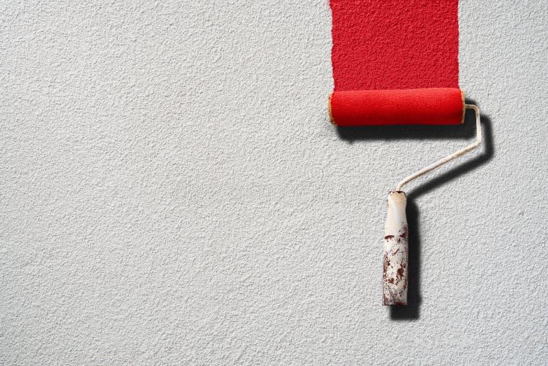 Ζωγραφική κυλίνδρων χρωμάτων με το κόκκινο χρώμα στον άσπρο τοίχο στοκ εικόνες