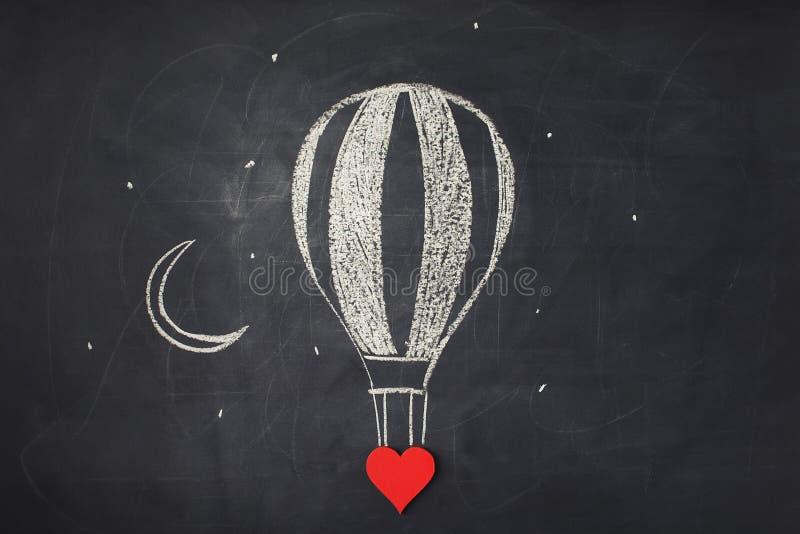 ζωγραφική Κόκκινη καρδιά και hand-drawn μπαλόνι ζεστού αέρα στον πίνακα κιμωλίας στοκ εικόνες