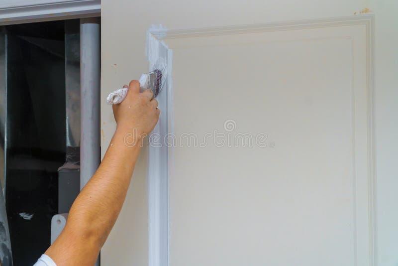 Ζωγραφική της ξύλινης πόρτας, του χεριού εργαζομένων και της βούρτσας στοκ εικόνα με δικαίωμα ελεύθερης χρήσης