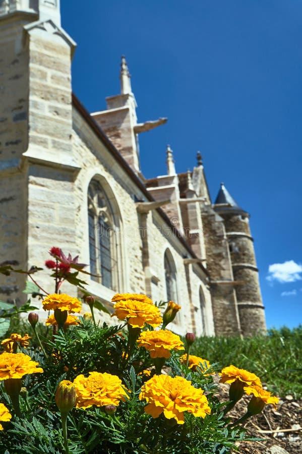 Ζωηρόχρωμα, ανθίζοντας λουλούδια και μια γοτθική εκκλησία στοκ φωτογραφία