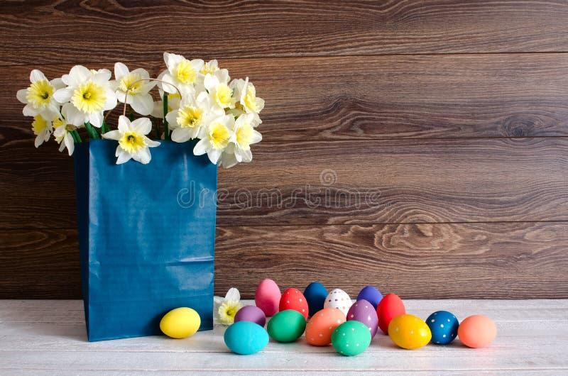 Ζωηρόχρωμα αυγά Πάσχας με την καλή ανθοδέσμη των ναρκίσσων σε μια μπλε τσάντα εγγράφου στο ξύλινο υπόβαθρο στοκ εικόνα