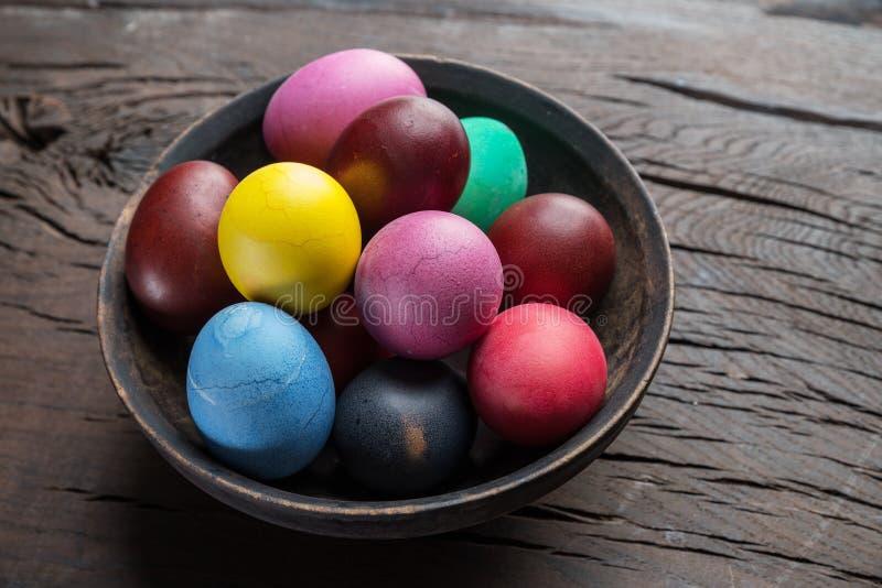 Ζωηρόχρωμα αυγά Πάσχας στο κύπελλο στον ξύλινο πίνακα Ιδιότητες του εορτασμού Πάσχας στοκ εικόνα με δικαίωμα ελεύθερης χρήσης