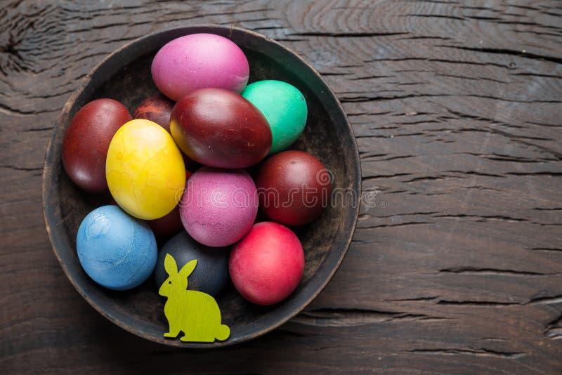 Ζωηρόχρωμα αυγά Πάσχας στο κύπελλο στον ξύλινο πίνακα Ιδιότητες του εορτασμού Πάσχας στοκ εικόνες