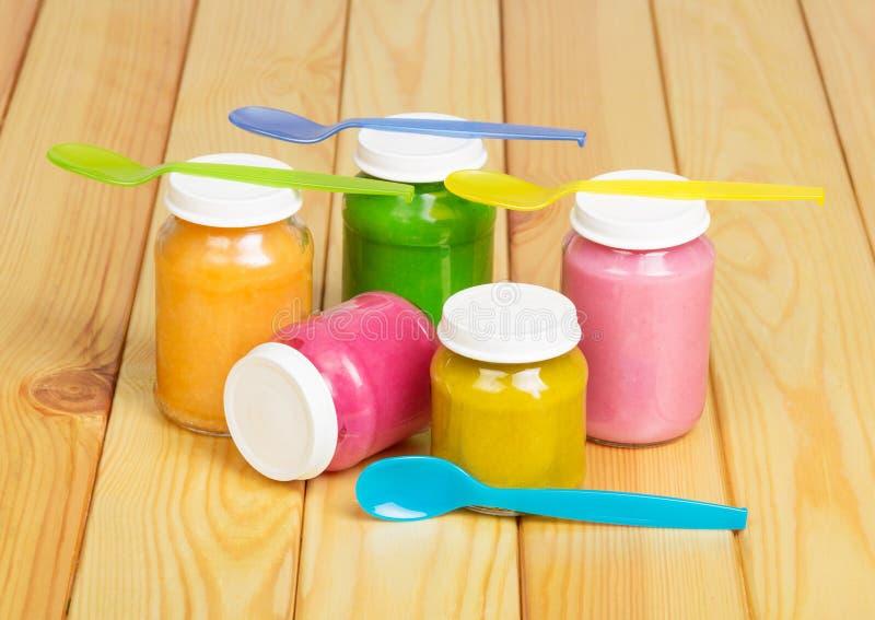 Ζωηρόχρωμα βάζα γυαλιού των παιδικών τροφών στο ελαφρύ ξύλο υποβάθρου στοκ φωτογραφίες