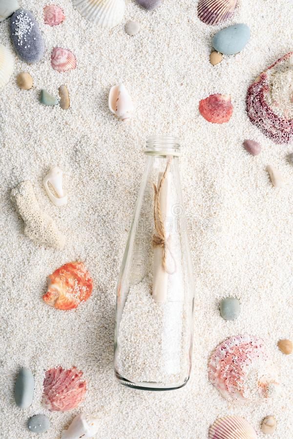 Ζωηρόχρωμα θαλασσινά κοχύλια & μπουκάλι με ένα μήνυμα στην άσπρη άμμο παραλιών στοκ φωτογραφία