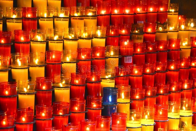 Ζωηρόχρωμα κεριά στο κόκκινο γυαλιού κυρίως στοκ εικόνα