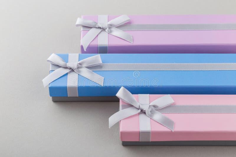 Ζωηρόχρωμα κιβώτια δώρων με τα τόξα κορδελλών στο γκρίζο υπόβαθρο στοκ εικόνα με δικαίωμα ελεύθερης χρήσης
