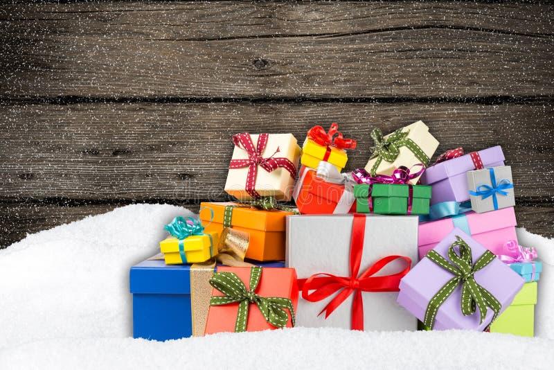 Ζωηρόχρωμα κιβώτια δώρων στο χιόνι στοκ εικόνα