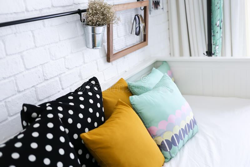 Ζωηρόχρωμα μαξιλάρια σε έναν καναπέ με τον άσπρο τουβλότοιχο ι στοκ εικόνα με δικαίωμα ελεύθερης χρήσης