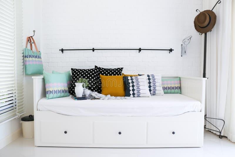 Ζωηρόχρωμα μαξιλάρια σε έναν καναπέ με τον άσπρο τουβλότοιχο ι στοκ εικόνες