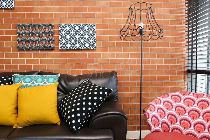 Ζωηρόχρωμα μαξιλάρια σε έναν καναπέ με το τουβλότοιχο στοκ φωτογραφία με δικαίωμα ελεύθερης χρήσης