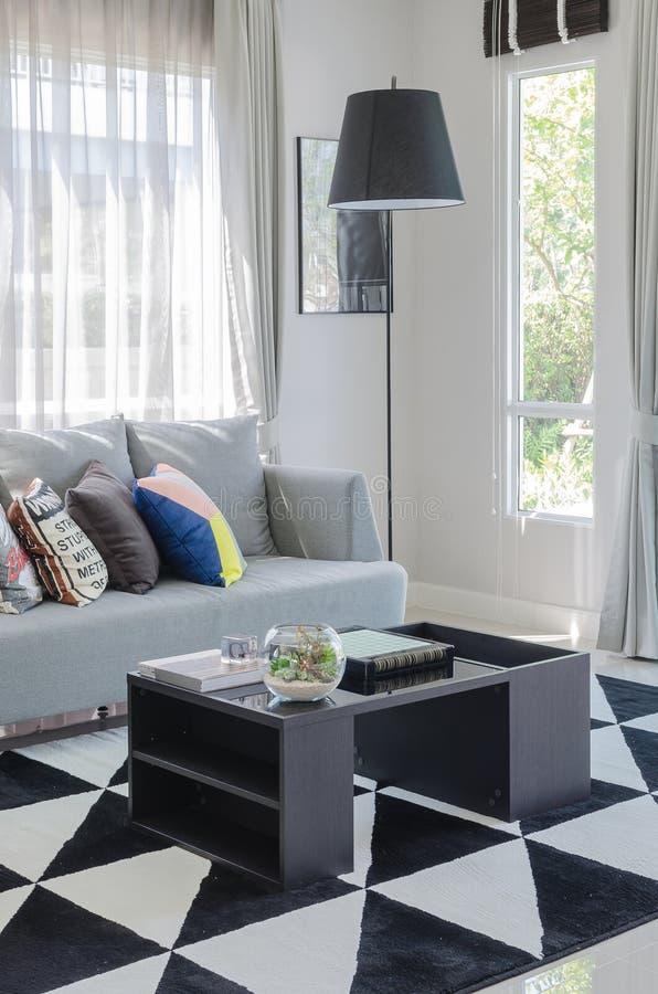 Ζωηρόχρωμα μαξιλάρια στο σύγχρονο γκρίζο καναπέ στο καθιστικό στοκ φωτογραφίες