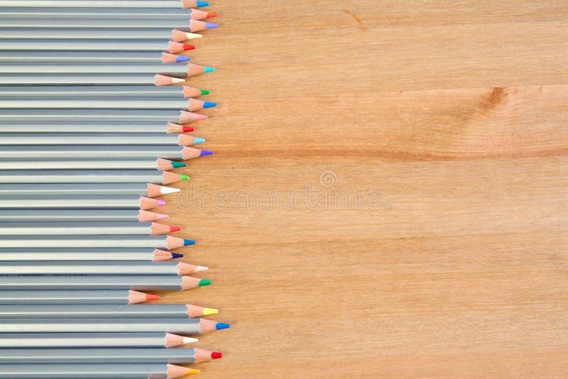 Ζωηρόχρωμα μολύβια στον ξύλινο πίνακα επίπεδος βάλτε το ύφος στοκ εικόνες