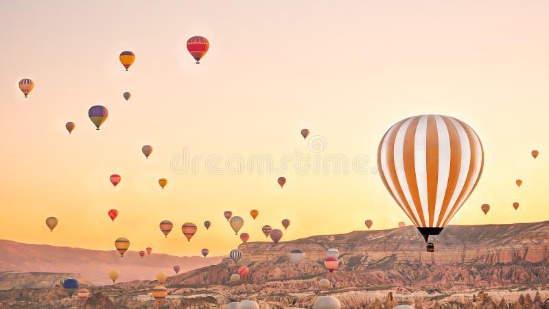 Ζωηρόχρωμα μπαλόνια ζεστού αέρα που πετούν πέρα από το τοπίο βράχου σε Cappadoc στοκ εικόνες με δικαίωμα ελεύθερης χρήσης