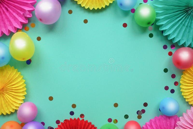Ζωηρόχρωμα μπαλόνια και λουλούδια εγγράφου στην μπλε άποψη επιτραπέζιων κορυφών Εορταστικό ή υπόβαθρο κομμάτων Επίπεδος βάλτε το  στοκ εικόνες