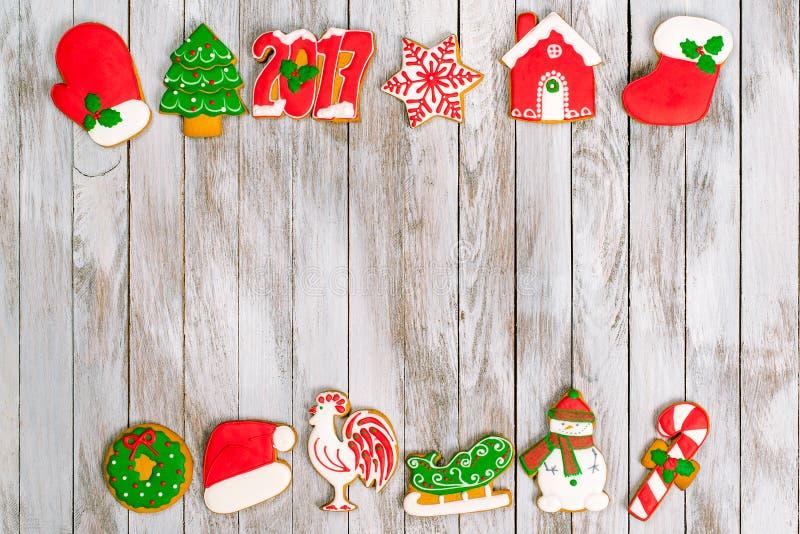 Ζωηρόχρωμα μπισκότα μελοψωμάτων Χριστουγέννων στο άσπρο ξύλινο backgroun στοκ φωτογραφίες