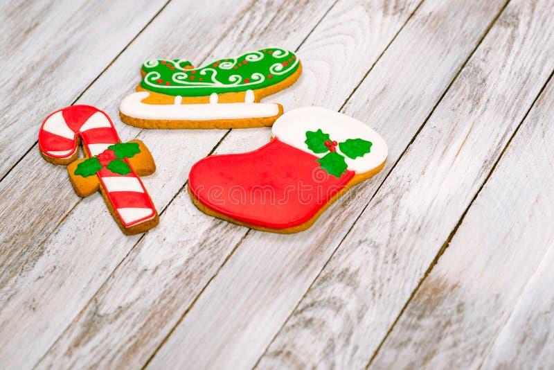 Ζωηρόχρωμα μπισκότα μελοψωμάτων Χριστουγέννων στο άσπρο ξύλινο backgroun στοκ εικόνα με δικαίωμα ελεύθερης χρήσης
