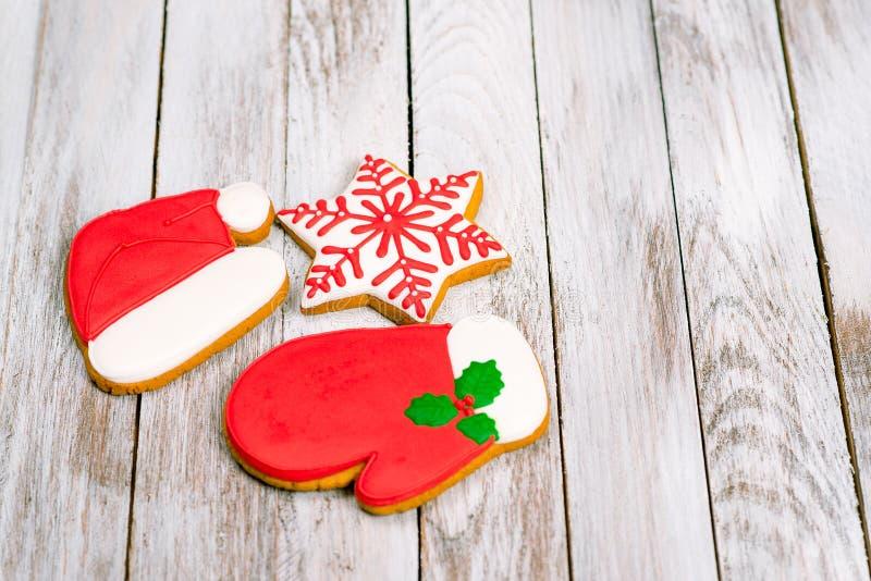 Ζωηρόχρωμα μπισκότα μελοψωμάτων Χριστουγέννων στο άσπρο ξύλινο backgroun στοκ εικόνες