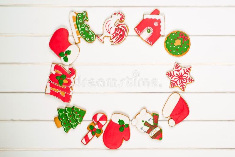 Ζωηρόχρωμα μπισκότα μελοψωμάτων Χριστουγέννων στο άσπρο ξύλινο backgroun στοκ φωτογραφία με δικαίωμα ελεύθερης χρήσης