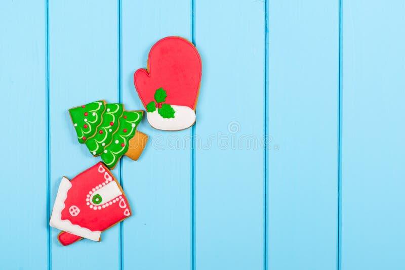 Ζωηρόχρωμα μπισκότα μελοψωμάτων Χριστουγέννων στο μπλε ξύλινο υπόβαθρο στοκ εικόνες