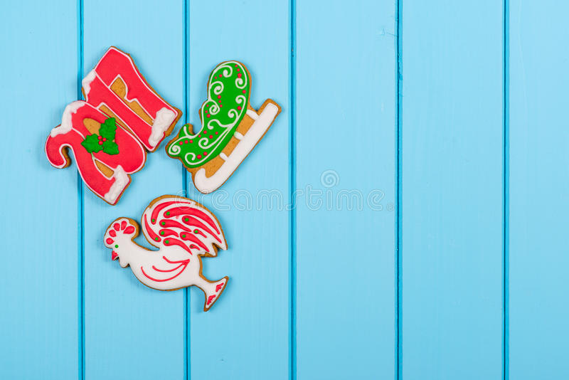 Ζωηρόχρωμα μπισκότα μελοψωμάτων Χριστουγέννων στο μπλε ξύλινο υπόβαθρο στοκ φωτογραφία με δικαίωμα ελεύθερης χρήσης