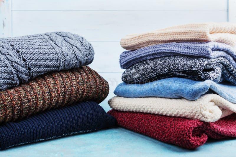 Ζωηρόχρωμα πουλόβερ μαλλιού και πλεκτά χειμερινά ενδύματα στο μπλε ξύλινο υπόβαθρο στοκ εικόνες