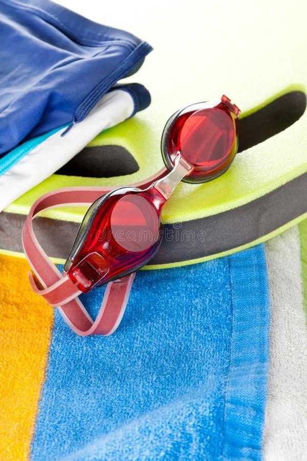 ζωηρόχρωμα προστατευτικά δίοπτρα παραλιών που κολυμπούν την πετσέτα στοκ φωτογραφία