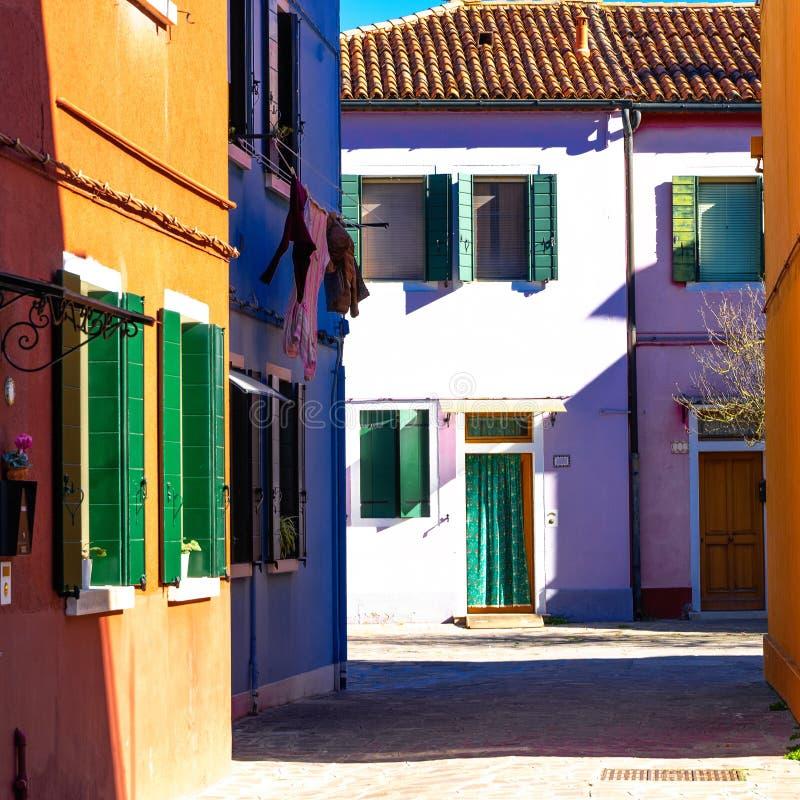 Ζωηρόχρωμα σπίτια του νησιού Burano Βενετία Χαρακτηριστική οδός με την ένωση του πλυντηρίου στις προσόψεις των ζωηρόχρωμων σπιτιώ στοκ εικόνα