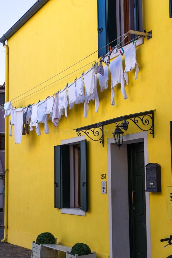 Ζωηρόχρωμα σπίτια του νησιού Burano Βενετία Χαρακτηριστική οδός με την ένωση του πλυντηρίου στις προσόψεις των ζωηρόχρωμων σπιτιώ στοκ φωτογραφίες με δικαίωμα ελεύθερης χρήσης