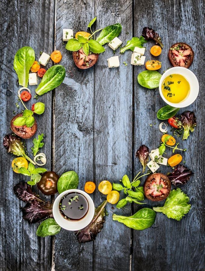 Ζωηρόχρωμα συστατικά σαλάτας με τις ντομάτες και τυρί φέτας στο αγροτικό μπλε ξύλινο υπόβαθρο, στρογγυλό πλαίσιο στοκ φωτογραφία με δικαίωμα ελεύθερης χρήσης