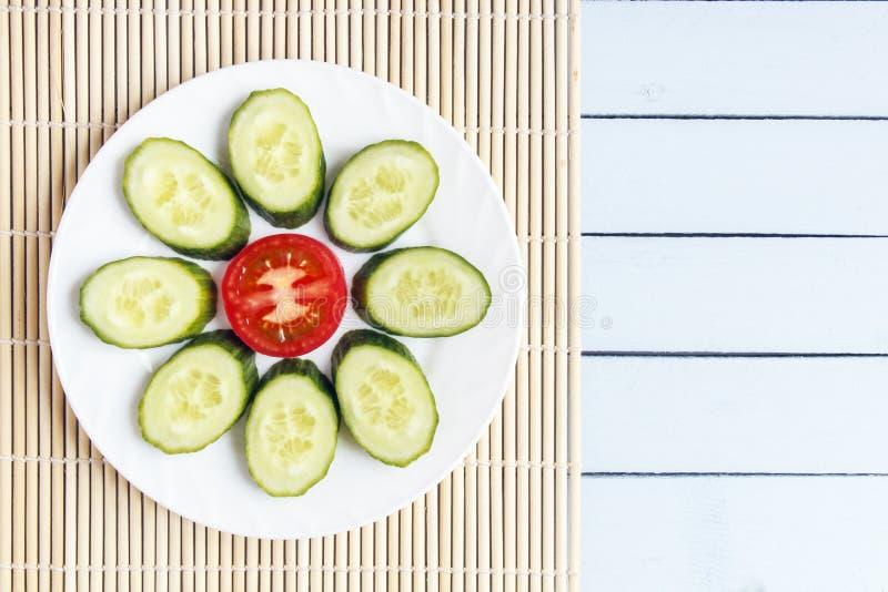 Ζωηρόχρωμα τεμαχισμένα φρέσκα οργανικά λαχανικά στο χαλί μπαμπού Ώριμα ντομάτα και αγγούρι με μορφή λουλουδιού Τοπ άποψη σχετικά  στοκ φωτογραφίες με δικαίωμα ελεύθερης χρήσης