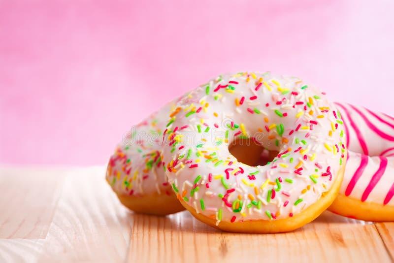 Ζωηρόχρωμα donuts στο φυσικό ξύλινο πίνακα και το ρόδινο υπόβαθρο στοκ φωτογραφία