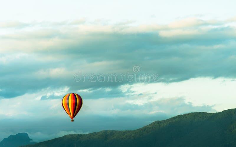 Ζωηρόχρωμα hot-air μπαλόνια που πετούν πέρα από το βουνό στοκ εικόνα