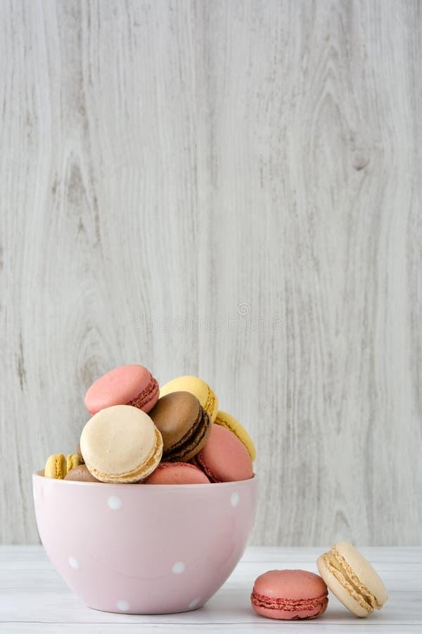 Ζωηρόχρωμα macarons σε ένα εκλεκτής ποιότητας κύπελλο στοκ εικόνες