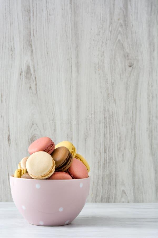 Ζωηρόχρωμα macarons σε ένα εκλεκτής ποιότητας κύπελλο στοκ φωτογραφία