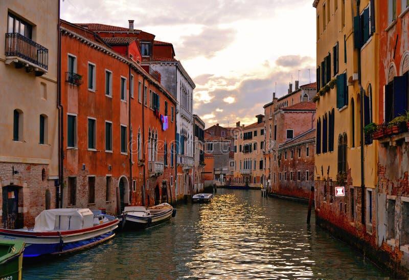 Ζωηρόχρωμες γωνίες της Βενετίας στο ηλιοβασίλεμα με τα παλαιές κτήρια και την αρχιτεκτονική, τις βάρκες και τις όμορφες αντανακλά στοκ εικόνα
