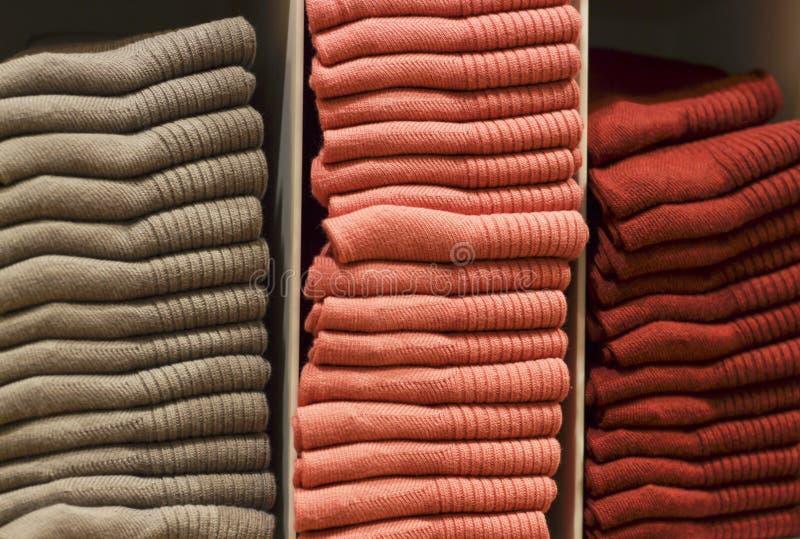 Ζωηρόχρωμες κάλτσες που συσσωρεύονται στο ράφι στο κατάστημα, υπόβαθρο των ενδυμάτων στοκ εικόνες