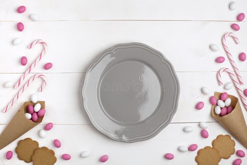 Ζωηρόχρωμες καραμέλες πλαισίων, ριγωτά lollipops και μπισκότα με το πιάτο Τοπ άποψη, άσπρο ξύλινο υπόβαθρο κόκκινος αυξήθηκε στοκ εικόνα
