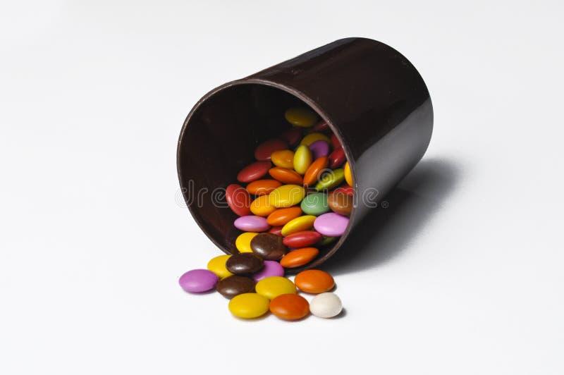 Ζωηρόχρωμες καραμέλες στα δοχεία που απομονώνονται στο άσπρο υπόβαθρο Ζωηρόχρωμες σφαίρες σοκολάτας στοκ φωτογραφία