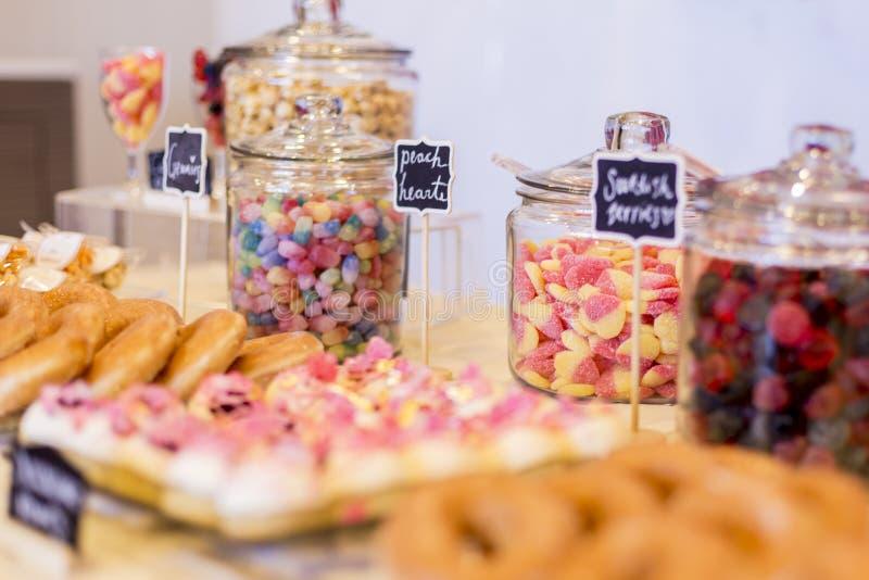 Ζωηρόχρωμες καραμέλες στα βάζα σε έναν πίνακα επιδορπίων με τα donuts, μπισκότα στοκ εικόνες