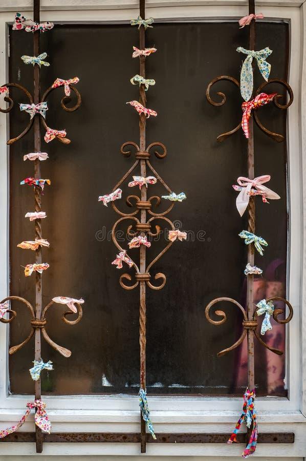 Ζωηρόχρωμες κορδέλλες με τους όρκους που αφήνονται από τους τουρίστες στους παλαιούς σκουριασμένους φραγμούς του παραθύρου Παραδό στοκ εικόνες με δικαίωμα ελεύθερης χρήσης