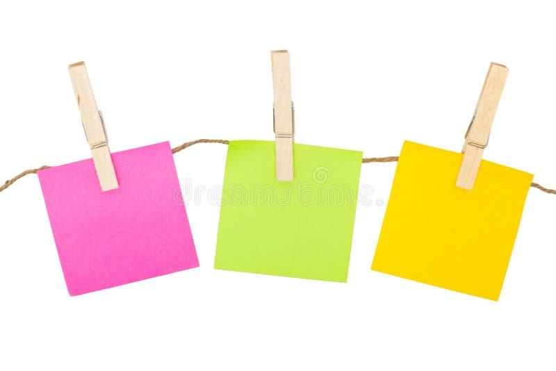 Ζωηρόχρωμες κολλώδεις σημειώσεις με Clothespins. στοκ φωτογραφία