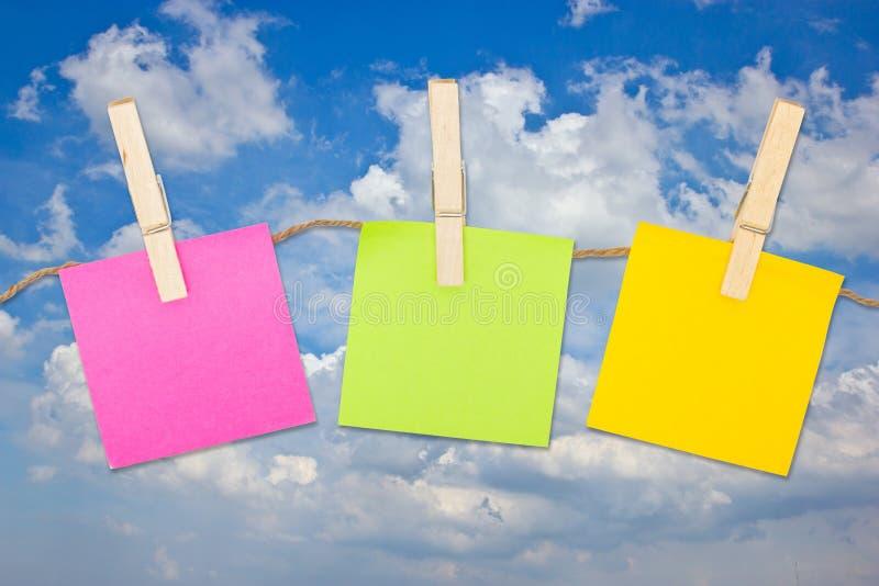 Ζωηρόχρωμες κολλώδεις σημειώσεις με Clothespins. στοκ εικόνες