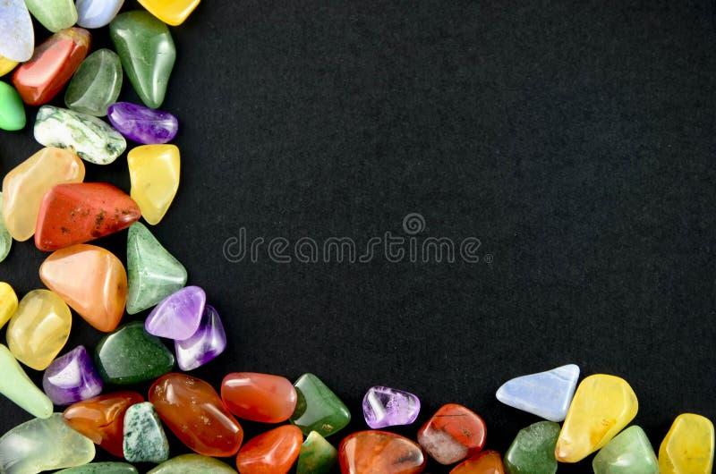 Ζωηρόχρωμες πέτρες κινηματογραφήσεων σε πρώτο πλάνο στο μαύρο υπόβαθρο στοκ φωτογραφίες
